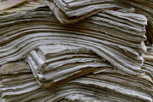 Stack old newspapers. Waste paper pile in vintage style. Abstract background. Close up. Environmental protection.